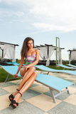 Gorgeous brunette girl with sexy long legs. Wearing black heels sitting on pool chair in bright sunny day Royalty Free Stock Photos