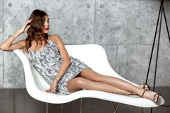 Gorgeous brunette girl in a wonderful gray evening dress is laying in a stylish white armchair against the gray wall royalty free stock image