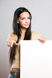 Gorgeous brunette holding empty banner. Stock Image