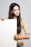 Gorgeous brunette holding empty banner. Stock Photo