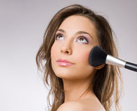Gorgeous brunette with makeup tools, brushes. Royalty Free Stock Photography