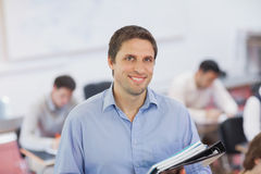 Gorgeous brunette male teacher posing in his classroom. Holding some files smiling at camera Royalty Free Stock Images