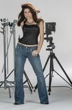 Gorgeous Brunette Model Poses In A Studio Environment Against A White Background Holding Camera Equipment. A beautiful brunette model posing in a studio royalty free stock images
