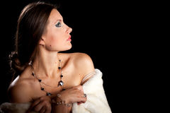 Gorgeous brunette model with winter fur on black background Stock Image