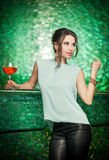Gorgeous brunette posing near a bright green bar stool. Attractive brunette woman with long hair in elegant light green blouse and black leather pants standing Stock Images
