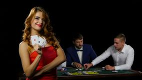 Gorgeous brunette in red dress shows off her two aces. In the background is seen the three men sitting at the poker table where laid cards and chips, slow stock video