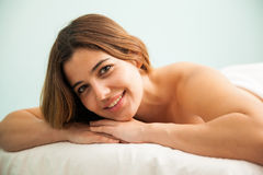 Gorgeous brunette in a spa bed. Portrait of a beautiful young Hispanic brunette laying on a massage bed at a spa and smiling, seen up close Royalty Free Stock Photos
