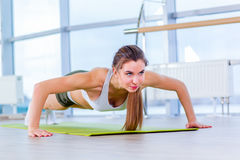 Gorgeous brunette warming up and doing some push ups a the gym Royalty Free Stock Images