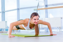 Gorgeous brunette warming up and doing some push ups a the gym Stock Image