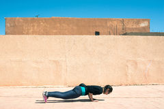 Gorgeous brunette warming up and doing some push ups, Marocco Royalty Free Stock Images