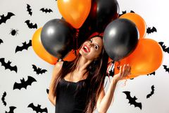 Gorgeous brunette woman in black dress holds black and orange balloons on a white background with black bats and spiders stock photo