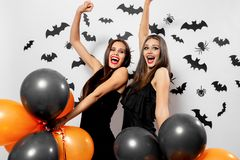Gorgeous brunette woman in black dress holds black and orange balloons on a white background with black bats and spiders stock photography