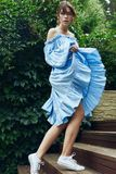 Gorgeous brunette woman in fashion blue dress in garden royalty free stock photo