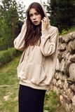 Gorgeous brunette woman in fashion hoodie in the garden alley royalty free stock images