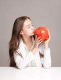 Gorgeous brunette woman holding piggy bank. Stock Image