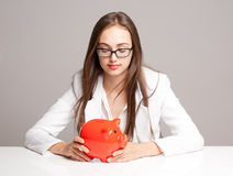 Gorgeous brunette woman holding piggy bank. Stock Image