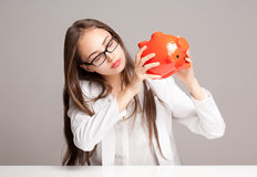 Gorgeous brunette woman holding piggy bank. Stock Images