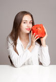 Gorgeous brunette woman holding piggy bank. Royalty Free Stock Photo