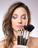 Gorgeous brunette woman with makeup tools. Stock Image
