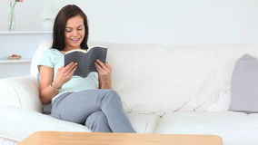 Gorgeous brunette woman reading a book while sitting on a sofa stock video