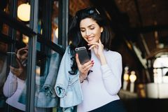 Gorgeous brunette woman in sunglasses dressed formally using cell phone flirting with handsome man on internet, waiting for his royalty free stock image