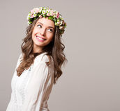 Gorgeous brunette woman wearing spring flower wreath. Portrait of a gorgeous brunette woman wearing spring flower wreath Royalty Free Stock Photo