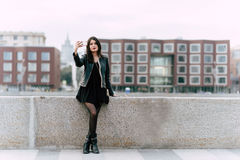 Gorgeous brunette women dressed in cool stylish clothes making self portrait with mobile phone camera Stock Image