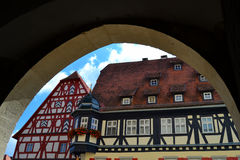 Gorgeous Buildings in Germany. Some beautiful half-timbered buildings with gable roofs in Rothenburg ob der Tauber seen through an arch. In the town district of Stock Photos