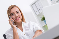 Gorgeous business lady on her phone. Smiling gorgeous businesswoman talking on her phone and looking to camera. Concept of business communication Royalty Free Stock Photography