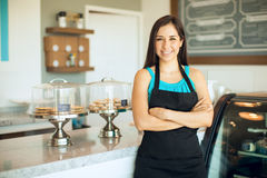 Gorgeous business owner in her shop. Cute Hispanic female business owner standing in front of her cake shop and smiling Royalty Free Stock Images