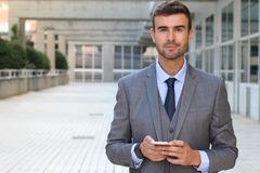 Gorgeous businessman holding a cell phone and smiling at camera.  Stock Image