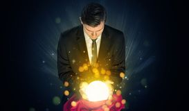 Businessman sitting with sparkling magic ball royalty free stock photography