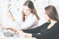 Gorgeous businesswomen using laptop at workplace Stock Images