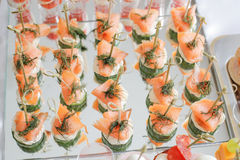Gorgeous canapes with smoked salmon and cucumber served on a mirror plate Royalty Free Stock Photography