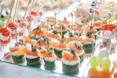 Gorgeous canapes with smoked salmon and cucumber served on a mirror plate Royalty Free Stock Photos