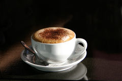 A gorgeous cappuccino. Cappuccino served in a ceramic cup against a dark background Stock Image