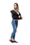 Gorgeous casual cutie wearing ripped jeans and black leather jacket looking back over shoulder. Stock Photos