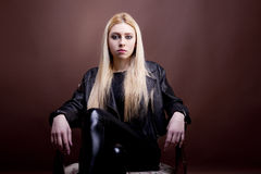Gorgeous caucasian girl in leather jacket sitting on vintage cha Royalty Free Stock Photography