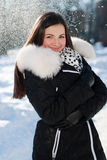 Gorgeous charming young woman standing in a black jacket in a snowy park outdoors on sunny day & looking at camera Royalty Free Stock Photos