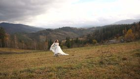 Gorgeous cheerful bride is running along the fantastic meadow. Beautiful nature lanscape of golden mountains. stock footage