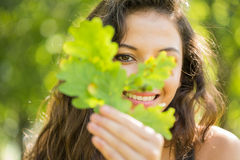 Gorgeous cheerful brunette holding a leaf Stock Photo