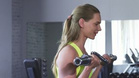 Gorgeous cheerful sportswoman doing biceps exercise at the gym royalty free stock photography
