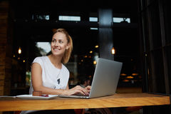 Gorgeous cheerful woman freelancer with good mood using laptop computer for distance work during lunch in cafe bar. Attractive female with beautiful smile Stock Photos