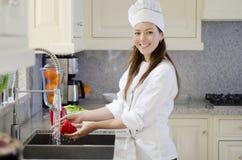 Gorgeous chef washing vegetables Stock Image