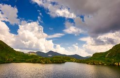Gorgeous cloudscape over the Capra lake. Amazing Fagaras mountain ridge in the distance Royalty Free Stock Image
