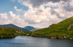 Gorgeous cloudscape over the Capra lake. Amazing Fagaras mountain ridge in the distance Stock Images