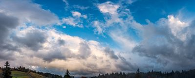 Gorgeous cloudscape over the forest on hills Royalty Free Stock Photo