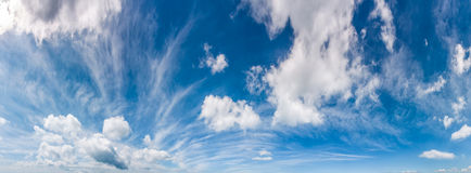 Gorgeous cloudscape panorama on a blue summer sky. Beautiful weather background with dynamic cloud arrangement Stock Image
