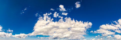 Gorgeous cloudscape panorama on a blue summer sky. Beautiful weather background with dynamic cloud arrangement Royalty Free Stock Photo