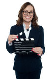 Gorgeous corporate woman holding a clapperboard Royalty Free Stock Photos
